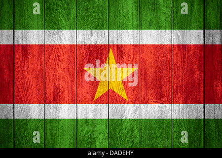 flag of Suriname or Surinamese banner on wooden background - Stock Photo