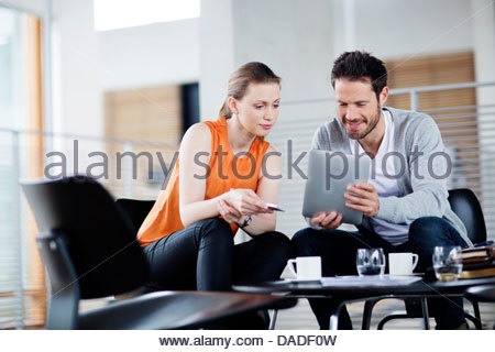 Man and woman using digital tablet - Stock Photo