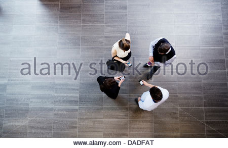 Four people using mobile phone - Stock Photo