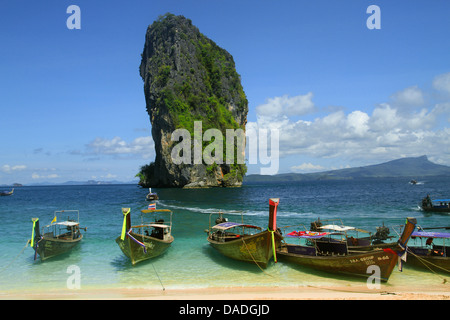 long-tail boats at the beach in front of grandiose karst rock formation, Thailand, Krabi, Laem Phra Nang - Stock Photo