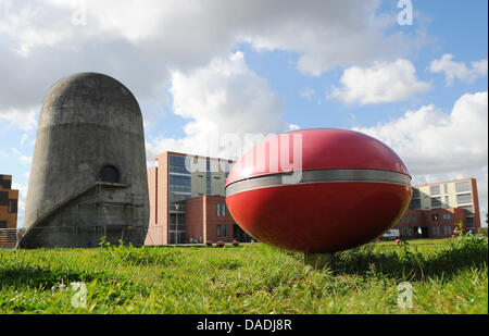 A red elliptical object that is a part of the sound installation AIRBORNE is situated in front of the Trudelturm - Stock Photo