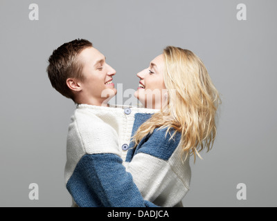 Young couple wearing same sweater - Stock Photo