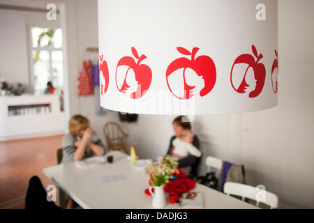 A young mother sits in the cafe 'Apfelkind' ('Apple Child') in Bonn, Germany, 27 October 2011. The Apple company - Stock Photo