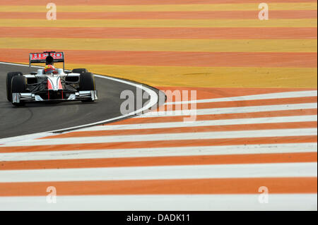 Indian Formula One driver Narain Karthikeyan of HRT steers his car during the first practice session at the race - Stock Photo