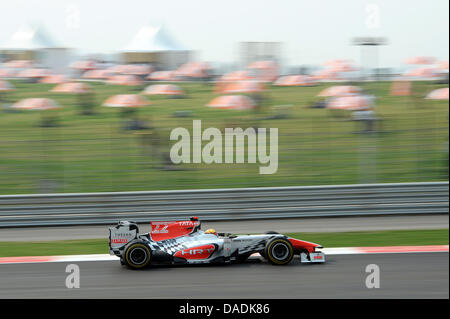 Indian Formula One driver Narain Karthikeyan of HRT steers his car during the second practice session at the race - Stock Photo