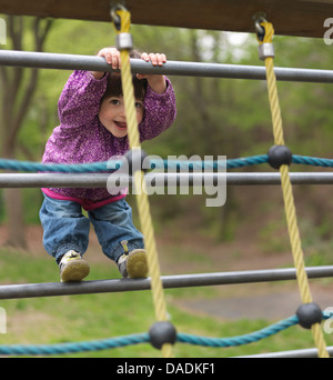 Young girl on climbing frame in playground, portrait - Stock Photo
