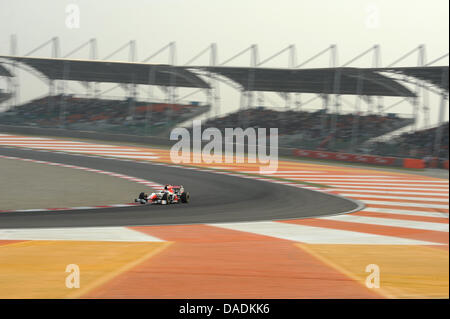 Indian Formula One driver Narain Karthikeyan of HRT steers his car during the qualification session at the race - Stock Photo