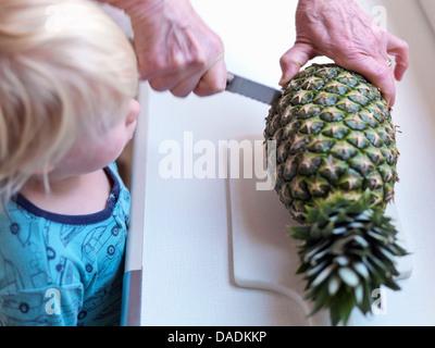 Boy watching woman slicing pineapple Stock Photo