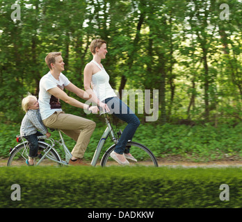 Family with one child riding on bicycle together - Stock Photo