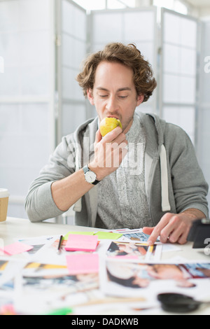Young man eating apple at desk in creative office - Stock Photo