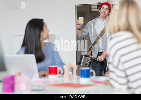 Young man arriving at meeting in creative office - Stock Photo