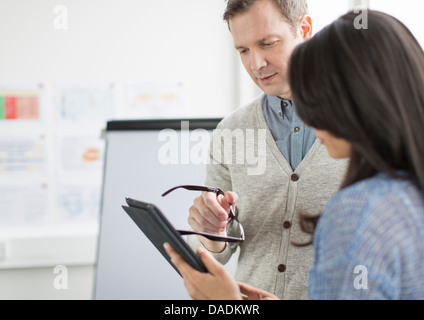Mature man and mid adult woman using digital tablet in creative office