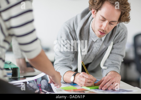 Young man making notes on desk in creative office - Stock Photo