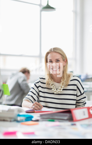 Young woman sitting at desk and smiling in creative office, portrait - Stock Photo