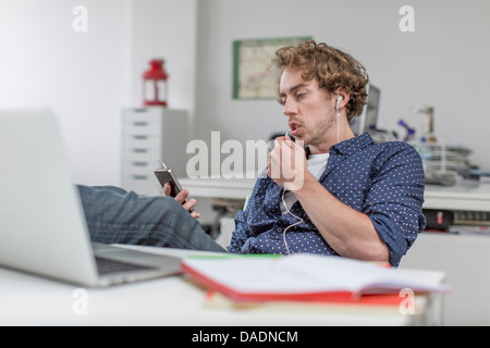 Young office worker listening to mp3 player at desk - Stock Photo