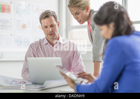 Business colleagues using laptop in meeting - Stock Photo