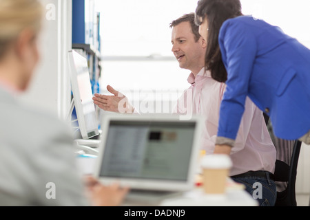 Business colleagues looking at computer monitor in office - Stock Photo