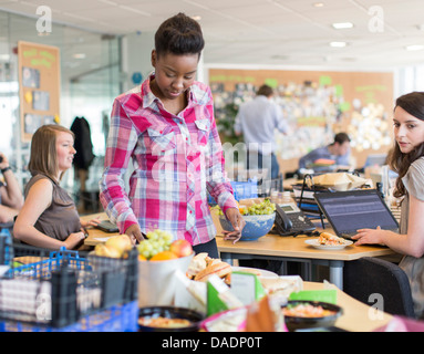 Young woman looking at fruit in creative office - Stock Photo