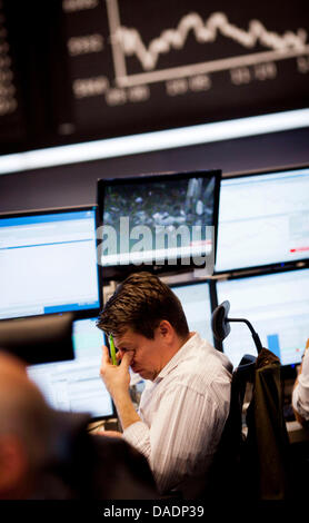 A sits underneath an board indicating the DAX index at the stock market in Frankfurt/Main, Germany, 1 November 2011. - Stock Photo
