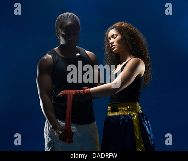 Young male wrapping female boxers hands with bandages - Stock Photo