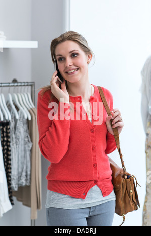 Young woman on mobile phone in fashion shop - Stock Photo