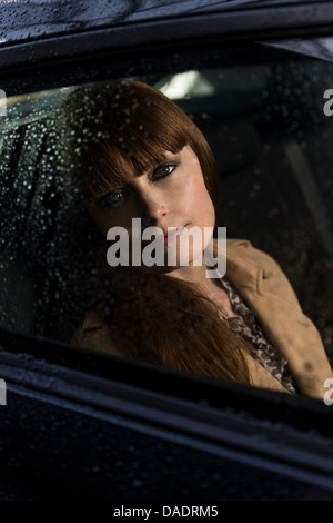 Business woman looking out of car window - Stock Photo