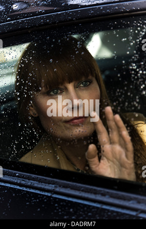 Woman waving and looking out of car window - Stock Photo