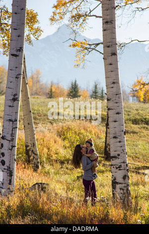 Mother holding toddler amongst silver birch trees - Stock Photo