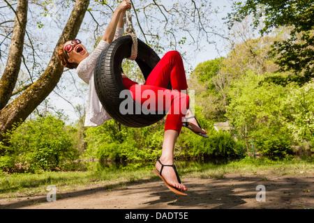 Young woman having fun on tire swing - Stock Photo