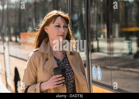 Woman with takeaway coffee next to city bus - Stock Photo