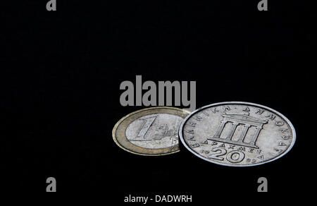 ILLUSTRATION - A Greek 20 drachm coin and a one-euro coin are pictured in Wuerzburg, Germany, 03 November 2011. - Stock Photo