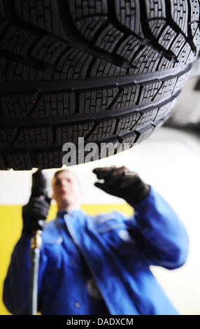 A mechanic mounts snow tires to a vehicle in Hamburg, Germany, 03 November 2011. Since last year, people are obliged - Stock Photo