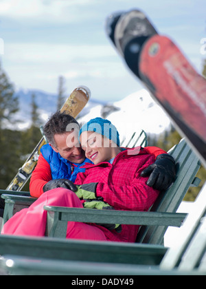 Mature man and young woman relaxing together in ski resort - Stock Photo