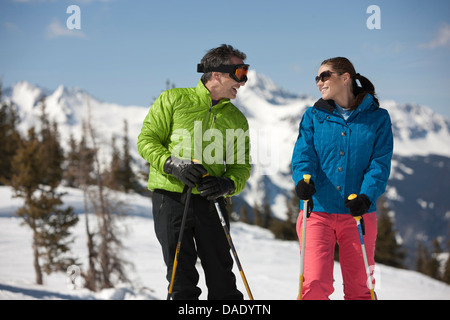 Young woman and mature man in skiwear holding ski poles - Stock Photo