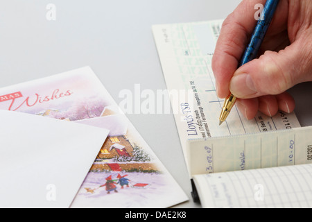 Senior female lady pensioner writing a Lloyds bank cheque as a gift to put in a Christmas card. England, UK, Britain. - Stock Photo