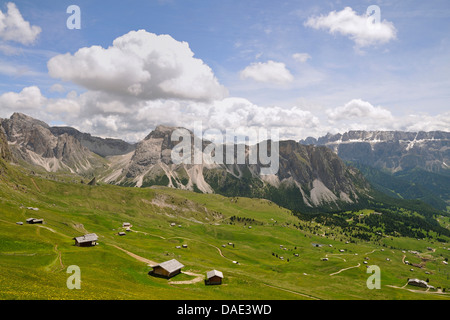 lots of alpine huts on mountain pasture in front of alpine panorama, Italy - Stock Photo