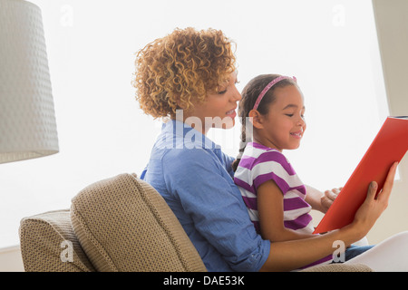 Mother with daughter reading book - Stock Photo