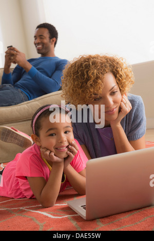 Mother and daughter using laptop - Stock Photo