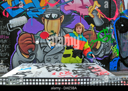 twelve-year-old boy playing table tennis in front of graffiti wall, Germany, North Rhine-Westphalia, Cologne - Stock Photo