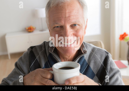Senior man with cup of coffee - Stock Photo