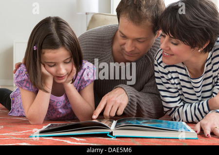 Daughter looking at picture book with parents - Stock Photo