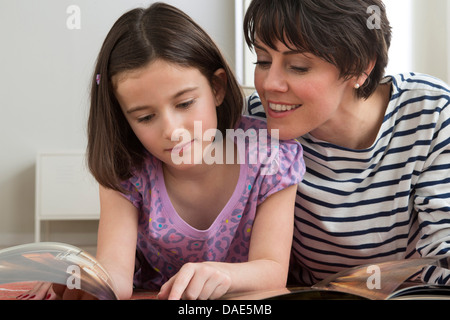 Daughter reading book with mother - Stock Photo