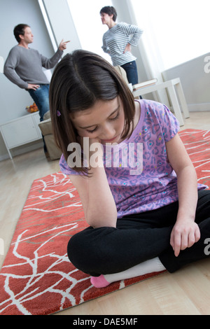 Girl sitting on floor with parents arguing in background - Stock Photo