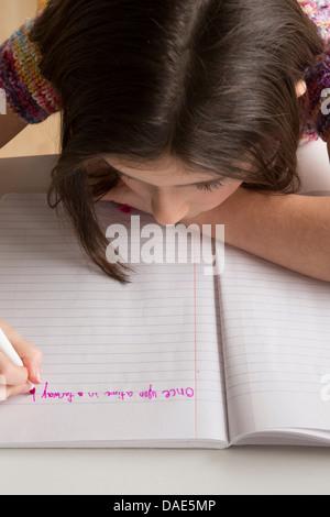 Girl writing in pink felt tip pen in notebook - Stock Photo