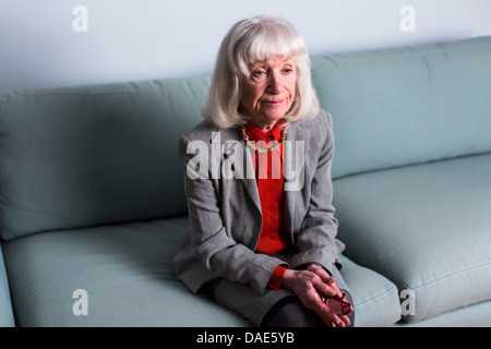 Senior woman sitting on sofa with blank expression - Stock Photo