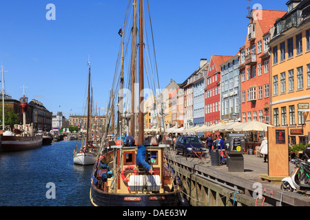 Old boats moored on canal with cafes and colourful buildings on 17th century waterfront in Nyhavn harbour Copenhagen - Stock Photo
