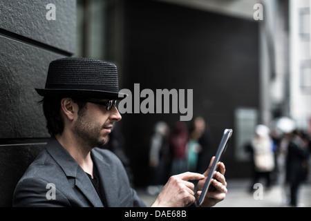 Portrait of man using digital tablet on city street - Stock Photo