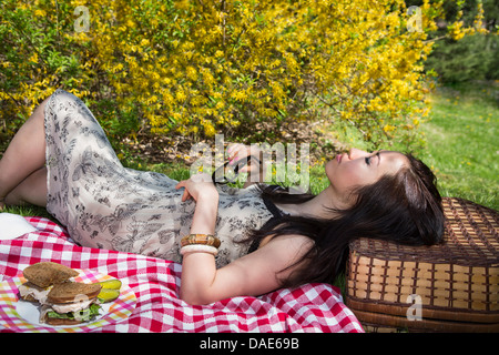 Woman lying on picnic blanket resting head on basket - Stock Photo