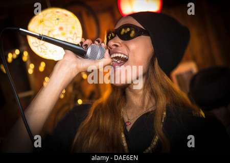 Woman wearing hat and sunglasses singing in microphone - Stock Photo