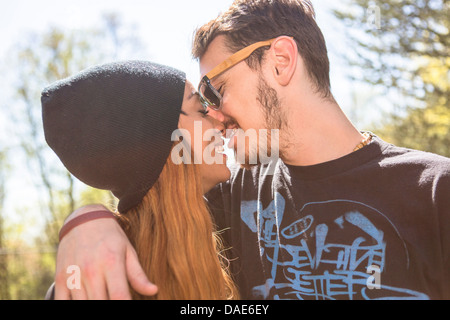 Couple kissing, woman wearing knit hat - Stock Photo